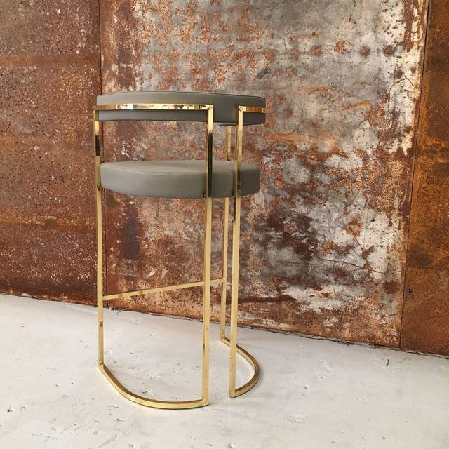 Upholstered in leather and featuring a curved polished brass frame that makes this furniture range so unique, this bar stool sets a very special scene for socialising. (...)
