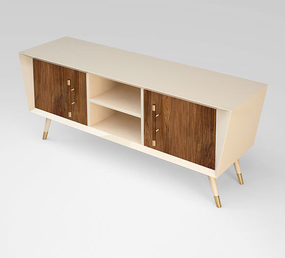 A handmade piece with a cream lacquer contrasting with American Walnut doors and tapered legs with brass detailing.